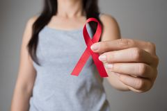 Closeup woman hand holding red ribbon HIV, world AIDS day awareness ribbon. Healthcare and medicine concept royalty free stock photos