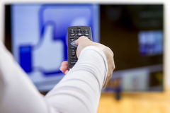 Closeup on woman hand holding remote control. And surfing internet on television. Focus on the remote control Stock Image