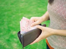 Business and financial, money saving concept. Closeup woman hand putting money into leather wallet . Business and financial, money saving concept Stock Photo