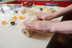 Closeup of woman hand with rolling baking cookies. Hands of the child knead the dough in the kitchen. dough, flour, baking tins on a white table in the Royalty Free Stock Photo