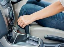 Closeup woman hand shifting the gear stick and driving a car. stock photos