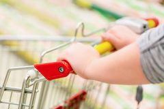 Closeup of woman hand with shopping cart in supermarket. Shopping concept. Selective focus royalty free stock photography