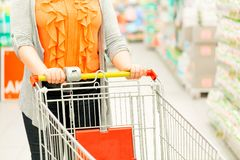 Closeup of woman hand with shopping cart in supermarket. Shopping concept. Selective focus royalty free stock images