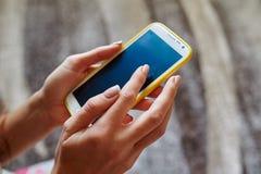 Closeup woman hand typing on smart phone Stock Photos