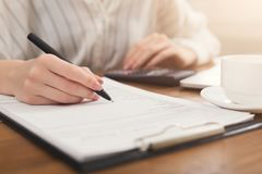 Closeup of woman hand writing in documents and using calculator Royalty Free Stock Photography
