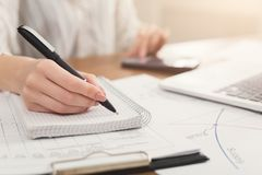 Closeup of woman hand writing notes and using calculator Royalty Free Stock Images