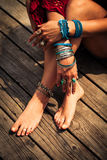 Closeup of woman hands and feet with boho summer fashion details. Young woman hands and feet with lot of boho fashion summer bracelets and rings outdoor shot on Royalty Free Stock Images