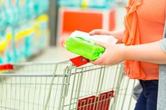 Closeup of woman hands with an item and shopping cart in supermarket. Shopping concept stock images