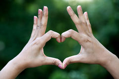 Closeup of woman hands making heart shape gesture Royalty Free Stock Photography