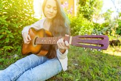 Closeup of woman hands playing acoustic guitar on park or garden background. Teen girl learning to play song and writing. Young hipster woman sitting in grass royalty free stock images