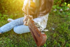 Closeup of woman hands playing acoustic guitar on park or garden background. Teen girl learning to play song and writing music royalty free stock photo