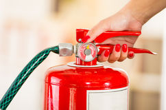 Closeup woman hands with red nailpolish showing how to operate fire extinguisher Stock Photos