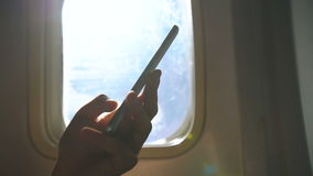 Closeup of woman hands sitting near airplane window using mobile phone during flight stock video footage
