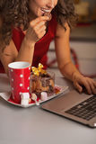 Closeup on woman having christmas cookies and usign laptop Royalty Free Stock Image