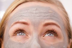 Closeup of woman having grey mud mask on face. Facial dry skin and body care, complexion treatment at home concept. Closeup of woman having grey mud mask on face Royalty Free Stock Photography