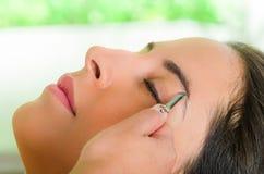 Closeup woman headshot profile,lying with eyes closed and hand holding tweezer pulling eyebrow Stock Photo