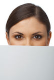 Closeup of a Woman Hiding Behind Billboard Royalty Free Stock Photography