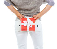 Closeup on woman hiding Christmas gift behind back. Closeup on woman hiding Christmas gift box behind back Royalty Free Stock Images