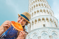 Closeup of woman holding and biting slice of pizza in Pisa Stock Photo