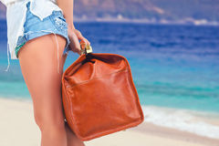 Closeup woman holding hand luggage, summer travel. Closeup woman holding hand luggage. Summer travel. Blue sea and white sandy beach at Bali. Vacation rentals Stock Images