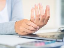 Closeup woman holding her hand pain from using computer long tim. E. Office syndrome concept stock image
