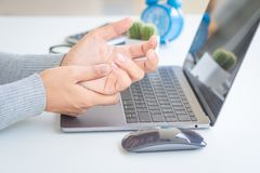Closeup woman holding her hand pain from using computer long tim Royalty Free Stock Image