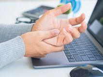 Closeup woman holding her hand pain from using computer long tim. E. Office syndrome concept stock images