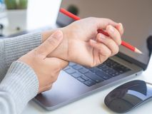 Closeup woman holding her wrist pain from using computer long ti Royalty Free Stock Photo