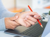 Closeup woman holding her wrist pain from using computer long ti. Me. Office syndrome concept royalty free stock photo
