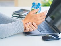 Closeup woman holding her wrist pain from using computer long ti. Me. Office syndrome concept stock photos