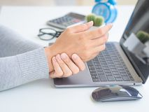 Closeup woman holding her wrist pain from using computer long ti. Me. Office syndrome concept royalty free stock photos