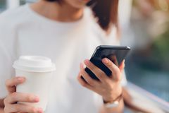 Closeup of woman holding a smartphone, mock up of blank screen. using cell phone on lifestyle. Technology for communication concept royalty free stock photo