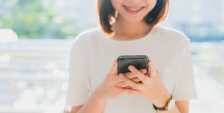 Closeup of woman holding a smartphone, mock up of blank screen. using cell phone on lifestyle. Technology for communication concept stock photography
