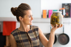 Closeup of woman holding up big jar of freshly-made dill pickles Stock Images