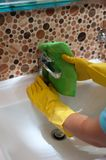 Female employee doing cleaning in bathroom. Closeup of woman housewife doing cleaning in the bathroom and wiping sink with rag stock photos