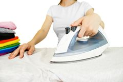 Closeup of woman ironing colored clothes on ironing board. House Royalty Free Stock Photo