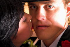 Closeup of woman kissing man. A closeup of a woman with dark hair, stretching up to kiss a blond man on the cheek royalty free stock photo