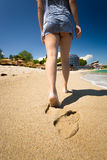Closeup of woman leaving footprints on sandy beach Stock Images