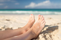 Closeup of woman legs on sea shore Stock Photos
