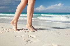 Closeup of woman legs on sea shore Stock Photos