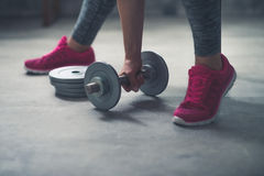 Closeup on woman lifting dumbbell from the floor Royalty Free Stock Images