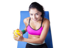 Closeup of woman lifting dumbbell on mattress Royalty Free Stock Photos