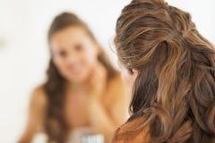 Closeup on woman looking in mirror in bathroom Royalty Free Stock Image