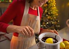 Closeup on woman making apple in chocolate glaze Stock Photos