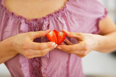 Closeup on woman making heart with strawberry