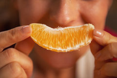 Closeup on woman making smile with orange slice Royalty Free Stock Image