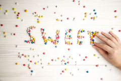 Closeup of woman making word Sweet from colorful candies Royalty Free Stock Photos