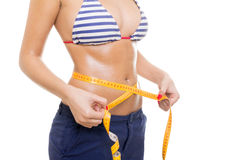 Closeup of woman measuring her waist Stock Photo