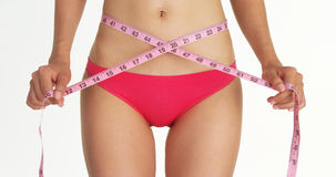 Closeup of woman measuring her waist with tape. White background Royalty Free Stock Image
