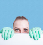 Closeup of woman medic hiding behind blank poster. With copy text space Royalty Free Stock Photography